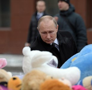 Russian President Vladimir Putin lays flowers at an impromptu memorial near the Zimnyaya Vishnya shopping mall in Kemerovo to honor those killed in the shopping mall fire