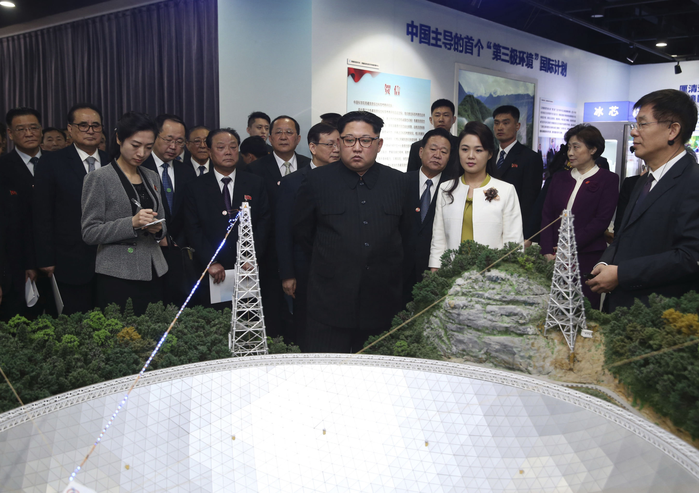 In this photo released Wednesday, March 28, 2018 by China's Xinhua News Agency, North Korean leader Kim Jong Un, center, and his wife Ri Sol Ju, visit an exhibition highlighting achievements by the Chinese Academy of Sciences.