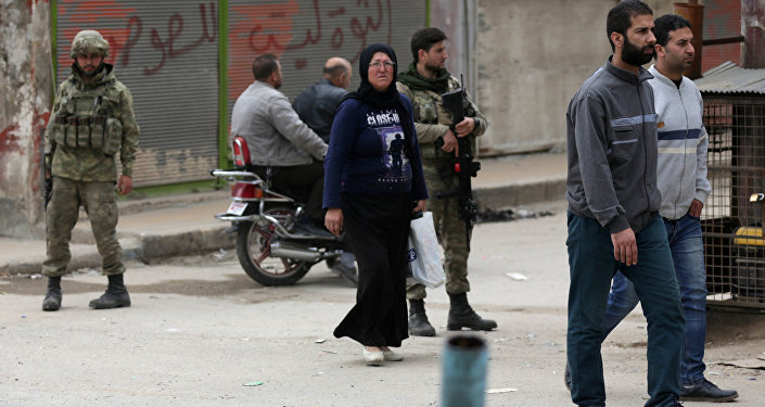 People walk as Turkish soldiers stand guard in the center of Afrin, Syria