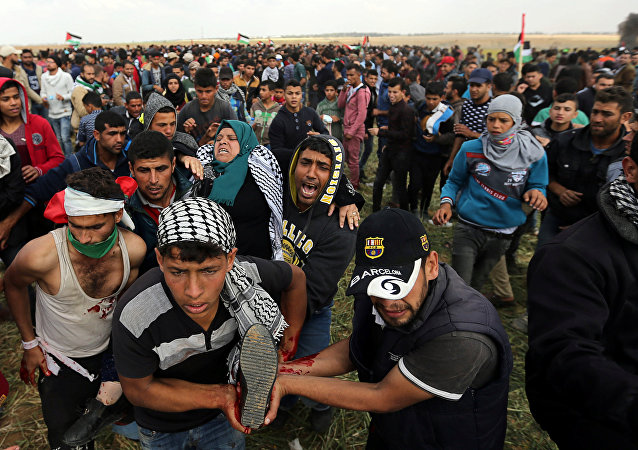 A wounded Palestinian woman is evacuated during clashes with Israeli troops, during a tent city protest along the Israel border with Gaza, demanding the right to return to their homeland, the southern Gaza Strip