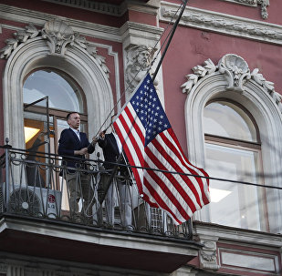 Diplomatic mission personnel remove a US flag from the building of the US Consulate-General on Furshtatskaya Street in St. Petersburg