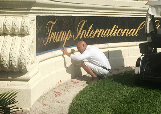A worker cleans up red paint from the stone sign at the entrance to the Trump International Golf Club in West Palm Beach, Fla., Sunday, April 1, 2018.