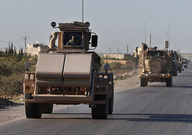 A U.S. mine detector armored vehicle, leads a convoy of U.S. troops, on a road leading to the tense front line with Turkish-backed fighters, in Manbij town, north Syria, Saturday, March 31, 2018