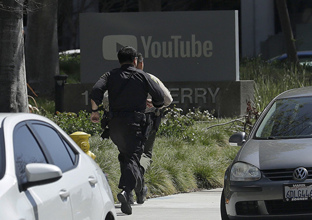 Officers run toward a YouTube office in San Bruno, Calif., Tuesday, April 3, 2018. Police and federal officials have responded to reports of a shooting Tuesday at YouTube headquarters in Northern California.