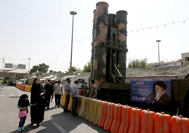 People walk past a Russian-made S-300 air defence system displayed on Baharestan square in Tehran on September 25, 2017
