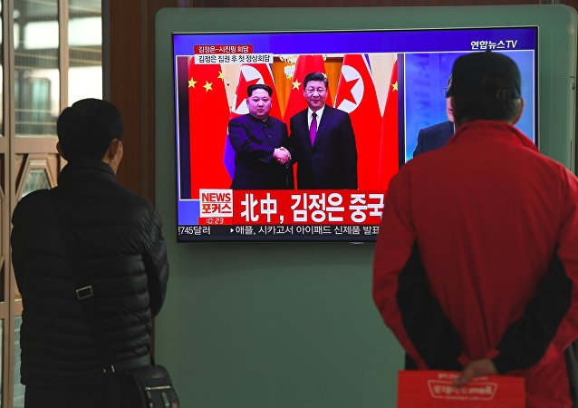 People watch a television news about a visit to China by North Korean leader Kim Jong Un, at a railway station in Seoul