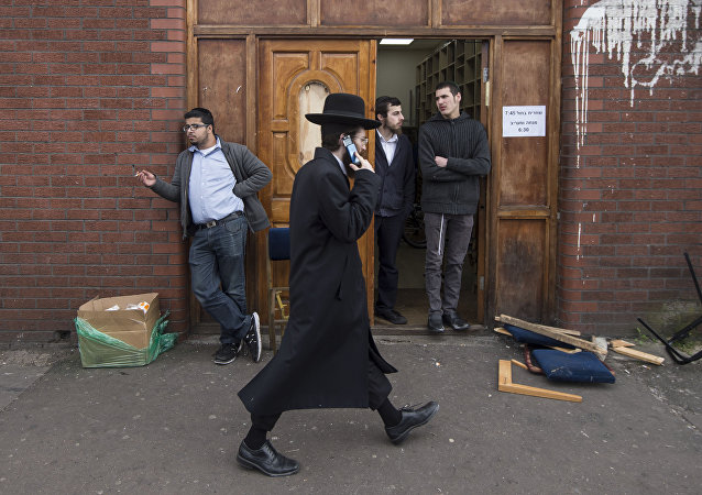 An Orthodox jew talks on his mobile phone as he walks past the Ahavas Torah synagogue in the Stamford Hill area of north London on March 22, 2015