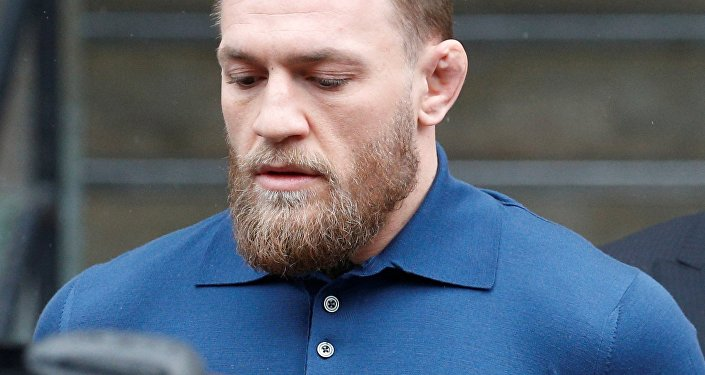 Ultimate fighting star Conor McGregor, center, is escorted by New York Court Police officers after a hearing at the Brooklyn Criminal Court, Friday, April 6, 2018, in New York