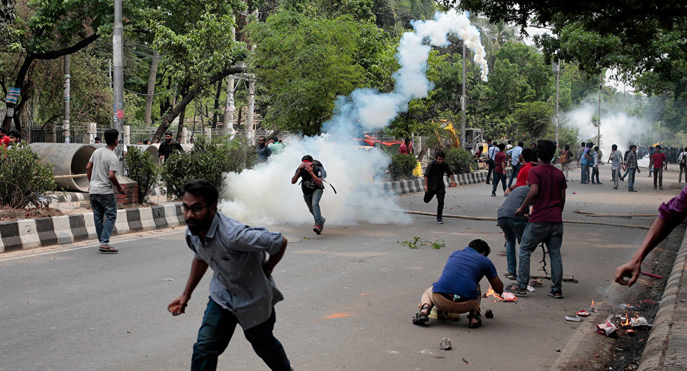 Bangladeshi students run for cover after policemen fire tear gas as they protest for removing or reforming a quota system in government jobs in Dhaka, Bangladesh, Monday, April 9, 2018
