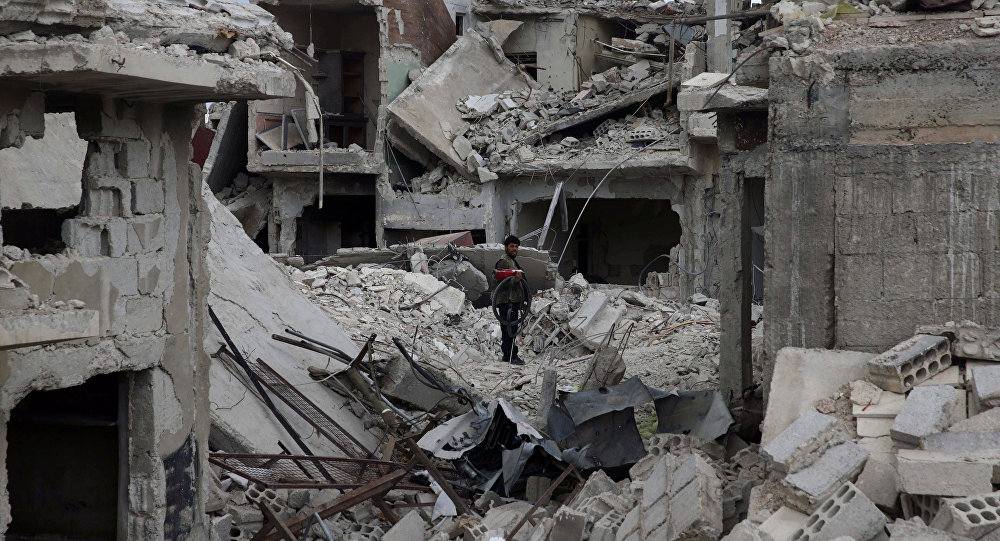 A man stands on rubble of damaged buildings in the besieged town of Douma, Eastern Ghouta, in Damascus, Syria March 30, 2018