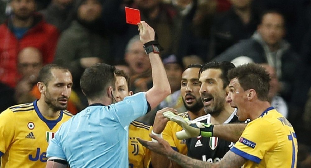 Referee Michael Oliver shows a red car to Juventus goalkeeper Gianluigi Buffon during a Champions League quarter final second leg soccer match between Real Madrid and Juventus at the Santiago Bernabeu stadium in Madrid, Wednesday, April 11, 2018