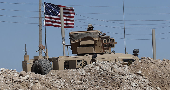 A U.S. soldier sits on an armored vehicle behind a sand barrier at a newly installed position near the tense front line between the U.S-backed Syrian Manbij Military Council and the Turkish-backed fighters, in Manbij, north Syria, Wednesday, April 4, 2018