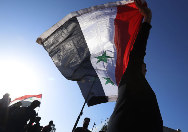 A Syrian government supporter holds up a Syrian national flag as he chants slogans against U.S. President Trump during demonstrations following a wave of U.S., British and French military strikes to punish President Bashar Assad for suspected chemical attack against civilians, in Damascus, Syria, Saturday, April 14, 2018