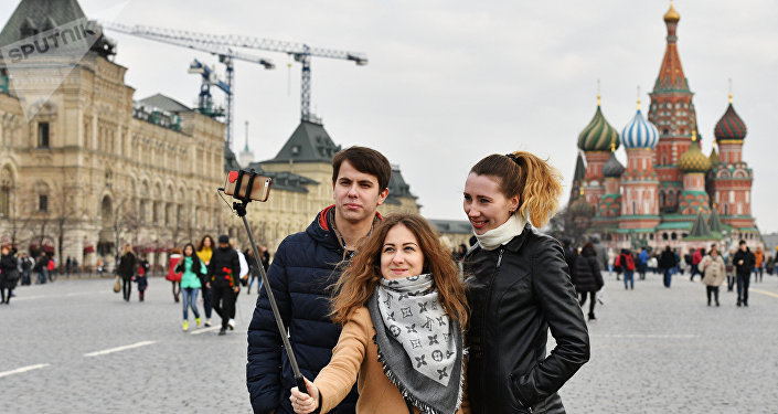 Tourists taking selfie on Red Square, Moscow. In the background St. Basil's Cathedral