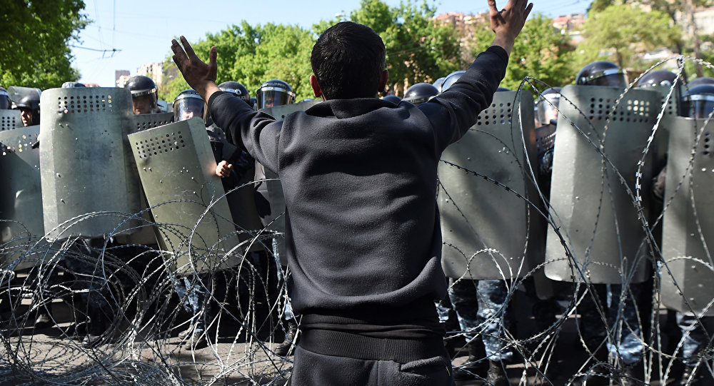 A demonstrator argues with riot police during a protest against Armenia's ruling Republican party's nomination of former President Serzh Sarksyan as its candidate for prime minister in Yerevan Armenia