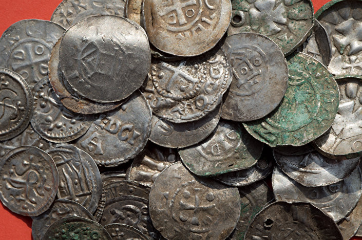 Saxon, Ottonian, Danish and Byzantine coins are pictured on a table in Schaprode, northern Germany on April 13, 2018. A 13-year-old boy and a hobby archaeologist have unearthed a significant trove in Germany which may have belonged to the legendary Danish king Harald Bluetooth who brought Christianity to Denmark