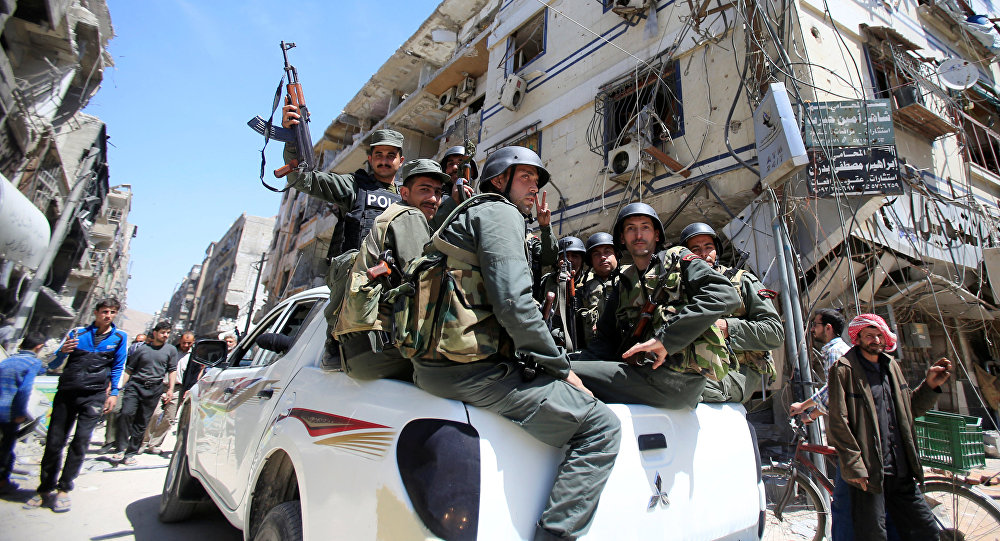 Members of the Syrian police hold their weapons as they sit on a back of a truck at the city of Douma, Damascus, Syria April 16, 2018