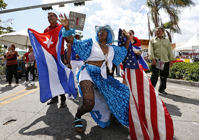 Lucina Michel, right, and her husband Caridad Osorio wave American and Cuban flags as they dance to music at the Calle Ocho Festival, Sunday, March 11, 2018, in Miami
