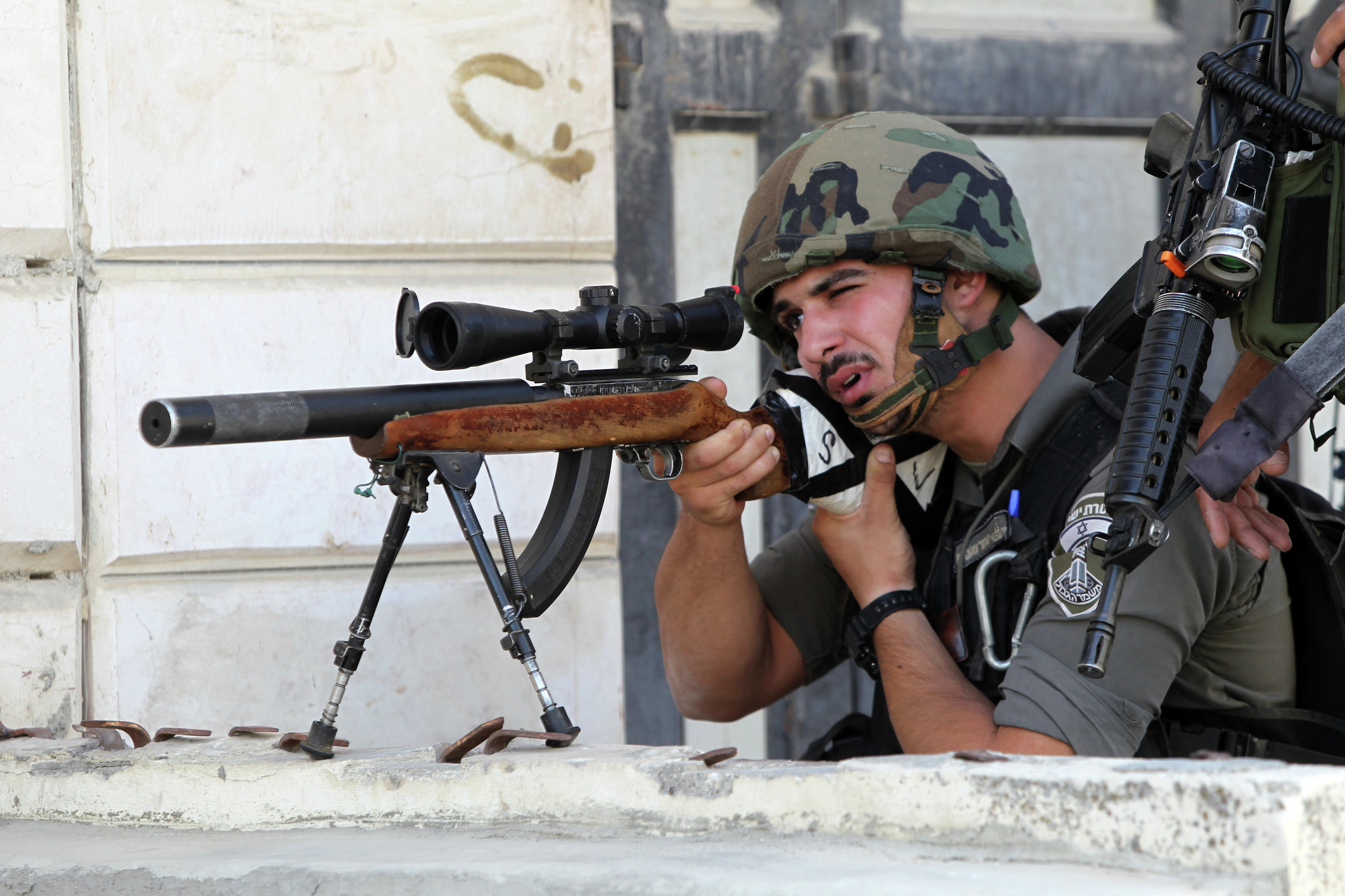 An Israeli border guard aims his sniper rifle during clashes with Palestinian protesters following an anti-Israeli protest after the weekly Friday prayers on September 18, 2015 in the Israeli-controlled area called H2, in the West Bank town of Hebron