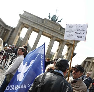 A protester holds a poster during the demonstration against airstrikes on Syria in Berlin, Germany