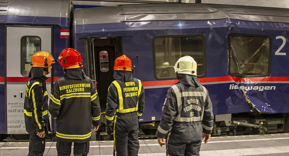 Fire fighters stand in front of two trains collided in the Salzburg, Austria, main station early Friday, April 20, 2018