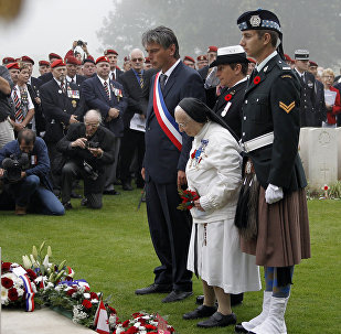 In this file photograph taken on August 19, 2012, Sister and former nurse Marie-Agnes Valois (C) lays down flowers in front of a memorial near Dieppe northwestern France, during the 70th anniversary ceremony of the Dieppe Raid, held in memory of the Second World War Allied attack on the German-occupied port of Dieppe on August 19, 1942