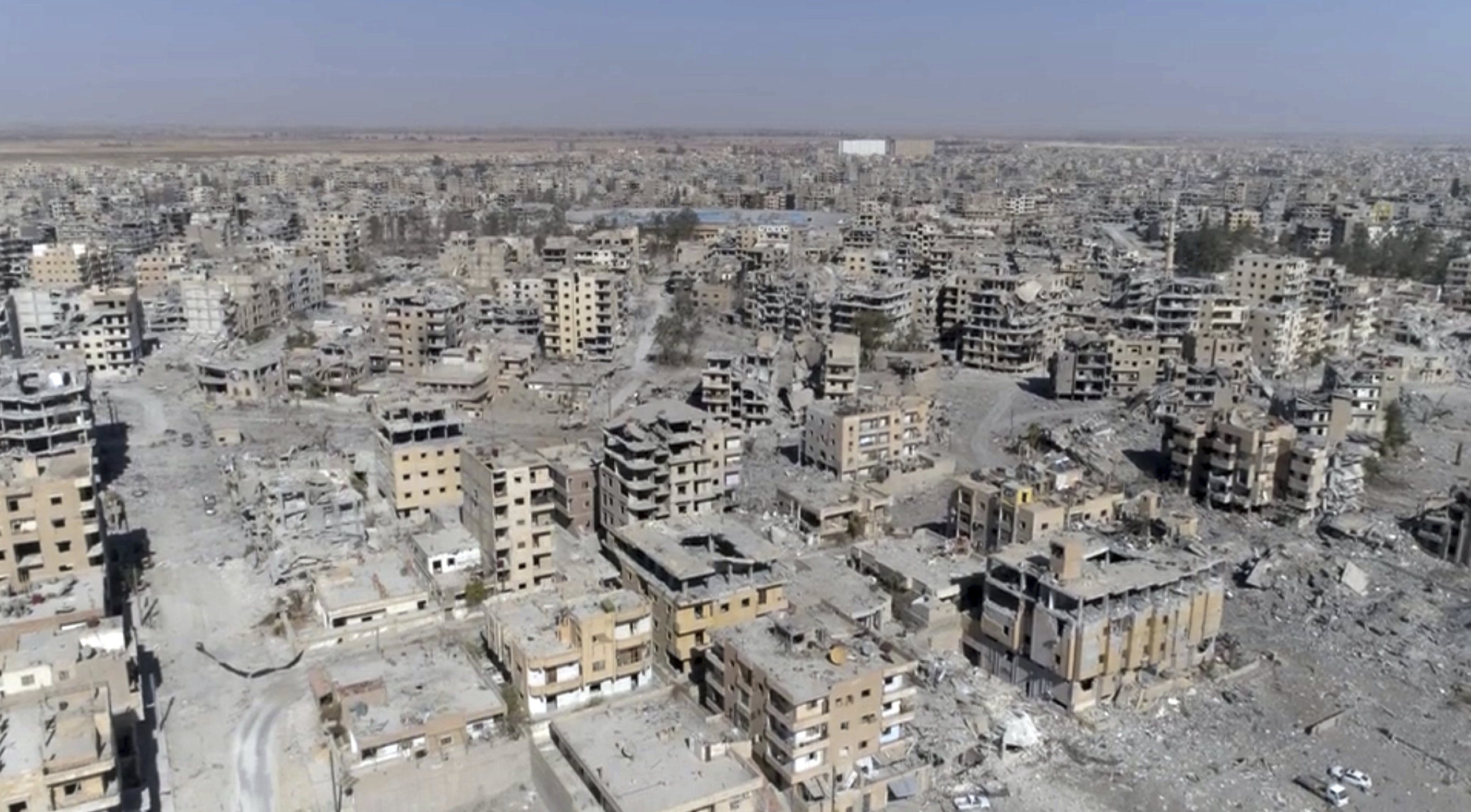 (File) This Thursday, Oct. 19, 2017 frame grab made from drone video shows damaged buildings in Raqqa, Syria