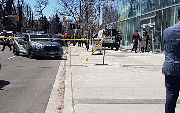 Police officers arrest suspect driver after a van hit multiple people at a major intersection in Toronto