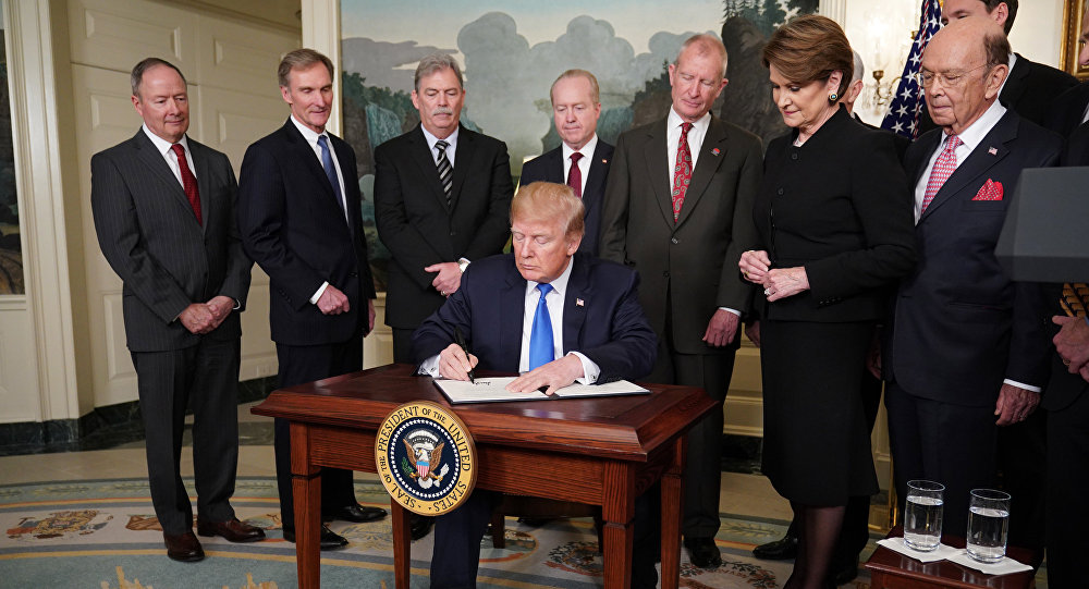 US President Donald Trump signs trade sanctions against China on March 22, 2018, in the Diplomatic Reception Room of the White House in Washington, DC, on March 22, 2018. Trump will impose tariffs on about $50 billion in Chinese goods imports to retaliate against the alleged theft of American intellectual property, White House officials said Thursday
