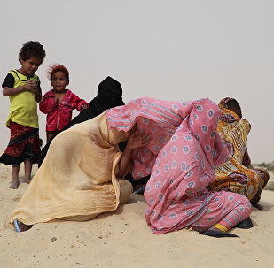 (File) In this photo taken on Thursday, Jan. 28, 2016, Tuareg woman and children gather near to homes that were burnt down, in Timbuktu , Mali