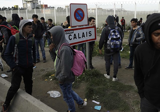 In this Thursday, Oct. 27, 2016 file photo migrants gather near a fence in Calais, northern France.
