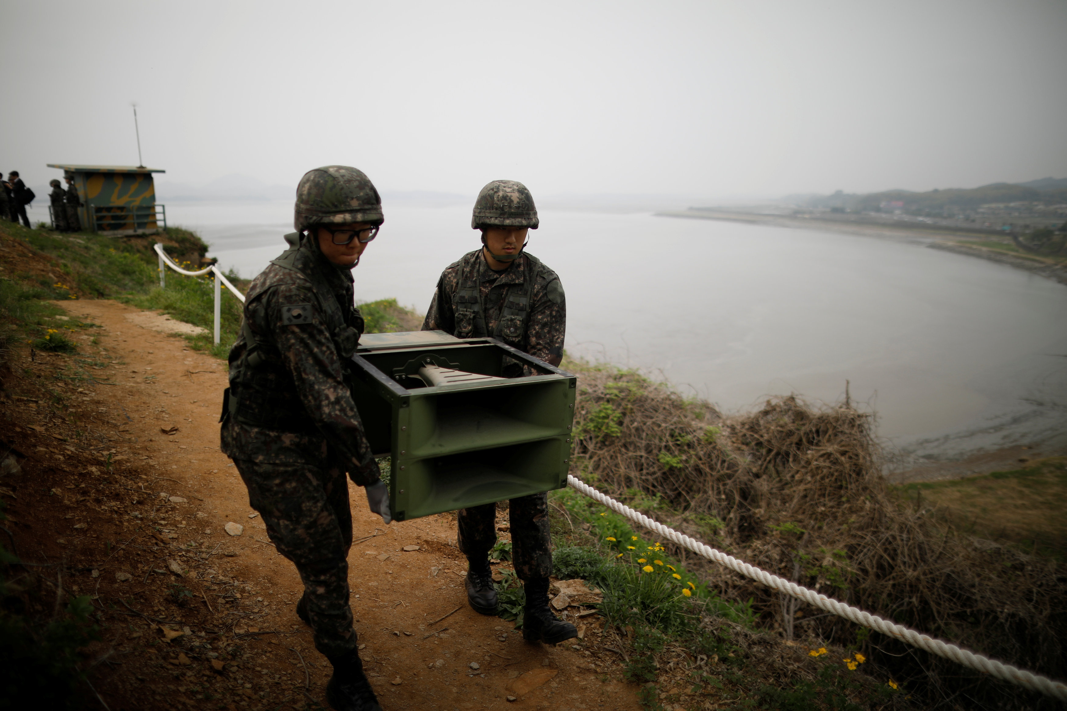 South Korean soldiers move loudspeakers that were set up for propaganda broadcasts near the demilitarized zone separating the two Koreas in Paju, South Korea, May 1, 2018.