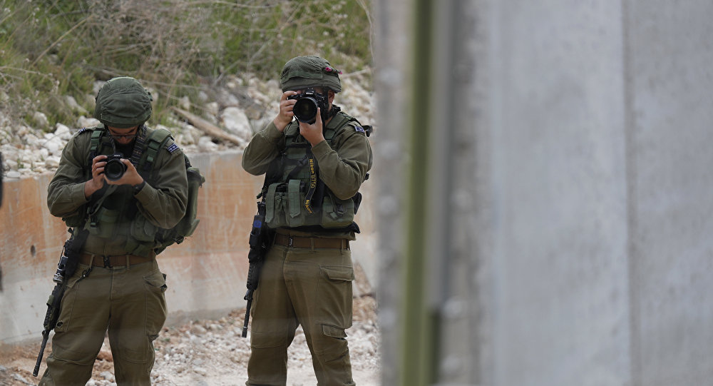 Israeli soldiers take pictures of construction work on a wall along the Israeli border, in the costal town of Naqoura, south Lebanon, Thursday, Feb. 8, 2018