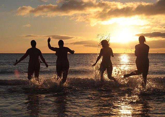 Nudists take part in the annual North East Skinny Dip as the sun rises at Druridge Bay in Northumberland, northeast England on September 22, 2013