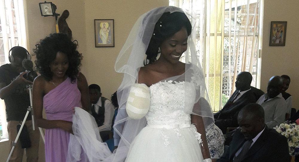 In this photo taken on Saturday, May, 5, 2018, Zenele Ndlovu walks down the aisle on her wedding day at a hospital Chapel in Bulawayo, Zimbabwe