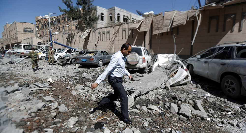 A man walks past damaged cars outside the Presidential Compound after it was hit by air strikes in Sanaa, Yemen May 7, 2018