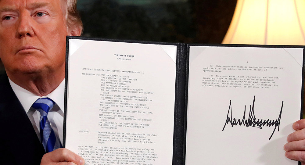 U.S. President Donald Trump holds up a proclamation declaring his intention to withdraw from the JCPOA Iran nuclear agreement after signing it in the Diplomatic Room at the White House in Washington