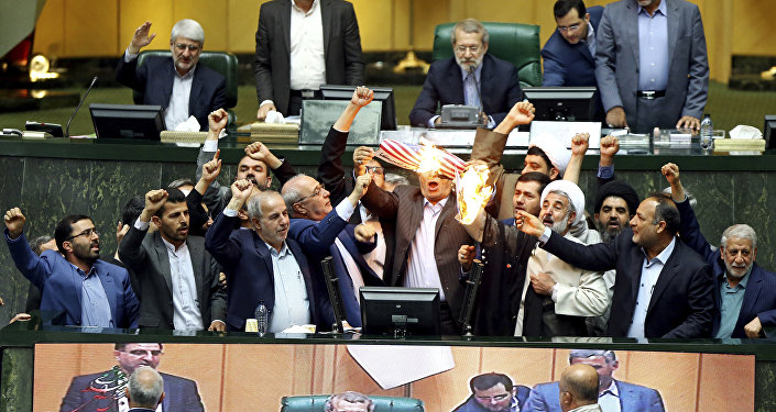 Iranian lawmakers burn two pieces of papers representing the U.S. flag and the nuclear deal as they chant slogans against the U.S. at the parliament in Tehran, Iran, Wednesday, May 9, 2018