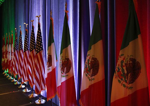 FILE - In this Aug. 16, 2017 file photo, the national flags of Canada, from left, the U.S. and Mexico, are lit by stage lights before a news conference, at the start of North American Free Trade Agreement renegotiations in Washington D.C. Mexico appears to be preparing for the worst as the fourth round of talks open in Washington D.C, Wednesday, Oct. 11, 2017