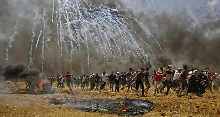 Palestinians run for cover from tear gas during clashes with Israeli security forces near the border between Israel and the Gaza Strip, east of Jabalia on May 14, 2018, as Palestinians protest over the inauguration of the US embassy following its controversial move to Jerusalem