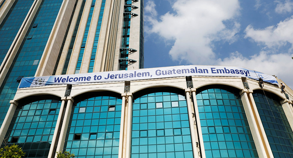 Workers hanging from the side of a building place a banner welcoming the opening of the new Guatemalan embassy in Jerusalem, in the complex hosting the new embassy in Jerusalem, May 15, 2018