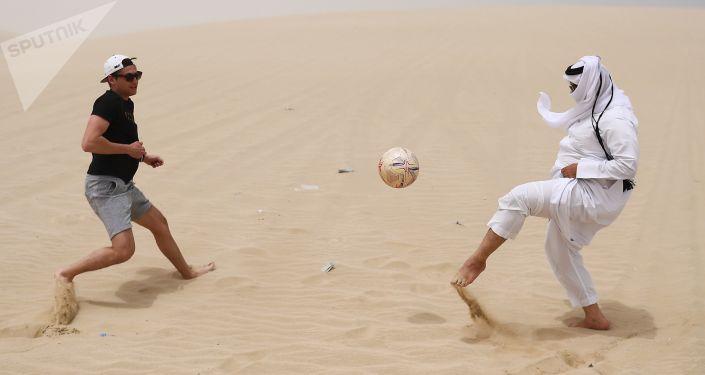 Мужчины играют в футбол в пустыне Khor Al Adaid в Дохе