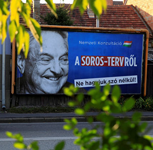 A man rides his moped past a government billboard displaying George Soros in monochrome next to a message urging Hungarians to take part in a national consultation about what it calls a plan by the Hungarian-born financier to settle a million migrants in Europe per year, in Szolnok, Hungary, October 2, 2017