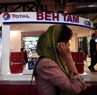 A businesswoman speaks on her mobile phone in front of the stand of French oil and gas company Total, at Iran's annual International Oil, Gas, Refining & Petrochemical Exhibition in Tehran, on May 6, 2014