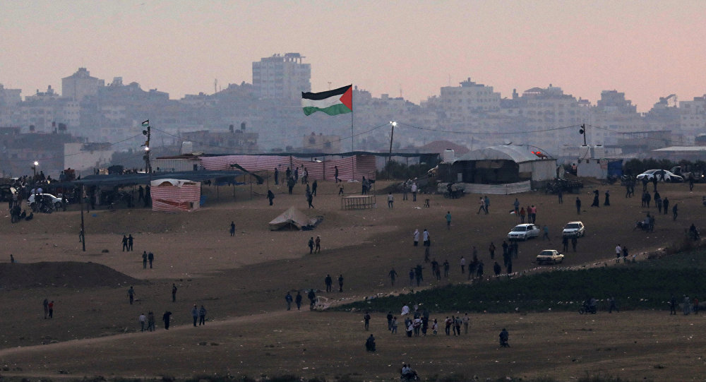 Palestinian protestors are seen next to the border fence between Israel, on the Gaza side of the border May 15, 2018