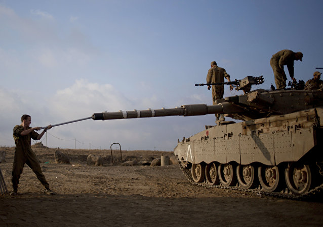 Israeli soldier work on a tank placed near the border with Syria on the Golan Heights (File)