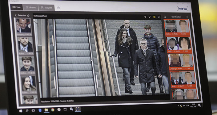 The screen of a computer with an automatic facial recognition system shows German Interior Minister Thomas de Maiziere (2ndR) walking down stairs as he visits the Suedkreuz train station where automatic facial recognition technologies are tested on December 15, 2017 in Berlin