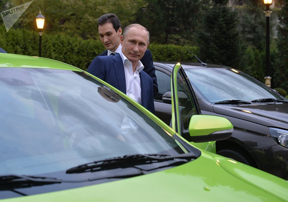President Vladimir Putin (foreground) taking his seat behind the wheel of the new AvtoVaz model Lada Vesta to drive to the International Valdai Discussion Club's 12th annual meeting at the Bocharov Ruchei residence in Sochi, October 22, 2015