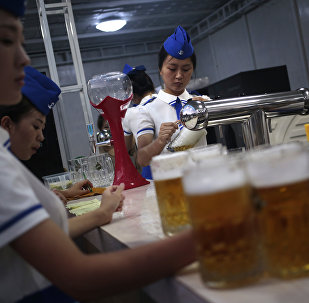 A waitress fill up jugs of beer during Taedonggang Beer Festival in Pyongyang, North Korea, Sunday, Aug. 21, 2016.
