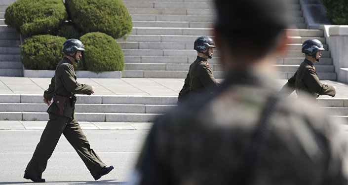 In this April 18, 2018 photo, North Korean soldiers march as a South Korean soldier, center, stands guard during a press tour at the border village of Panmunjom in the Demilitarized Zone, South Korea